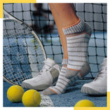 image of a woman wearing ankle height tennis socks that are hand knitted in regia self striping yarn in colors of white, grey, and peach  from the regia journal 4009 sock pattern pamphlet