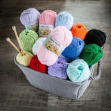 a pile of mary maxim in a fabric yarn basket on wood background, the yarn is a fine fingering weight yarn in a solid color with pastel pinks and bright crayon colors