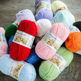pile of mary maxim fingering yarn in solid pastel colors and bright primary colors a plain ply that will show off stitches