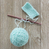 close up image of a ball of mint blue fingering weight yarn and a crocheted swatch on a small needle against a wood background