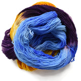 hank dyed sock yarn on a white background piled onto itself. Nerest us its showing a like sky blue, behind tha underneath the blue we can see a rich dark purple and bright sunshine yellow swirling around.