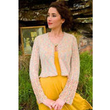 standing woman wearing a lightweight knitted cardigan with a high button on the rounded scoop neck. with lace sleeves and a more solid body this is 'Dijon'  from the Louisa Harding Winter's Muse Portraits Pattern Book