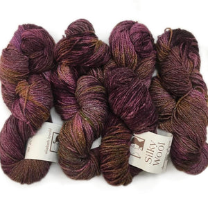four twisted hanks of silk and wool blend in soft mottled colors of mauve pink brown and gold. The orginal labels of elsebeth lavolds silky wool are still showing on the hank