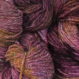 close up of yarn hanks showing a tweedy fiber with a pronounced ply the colors are mauve dark plum purple and golden brown