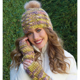 woman wearing a super bulky knit hat with vertical cables and garter stitch top with furry light brown pom pom and matching wrist warmers in colors of yellow green and grey
