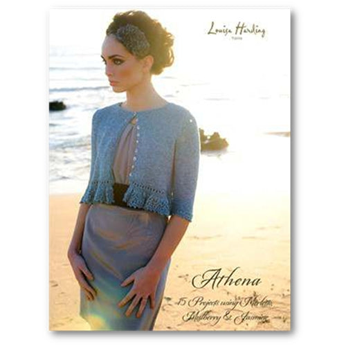 Cover of Louisa Harding's Athena Pattern Book #108. A Woman stands on the beach wearing a blue knit cardigan which is buttoned at the top button only and trimmed with lace