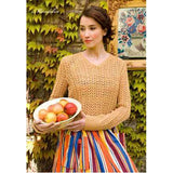 woman wearing a long sleeve v-neck knitted sweater with a lacy v-pattern along the body and sleeves, she's wearing a bright striped skirt and holding a bowl of fruit the pattern is 'Mandolin'  from the Louisa Harding Winter's Muse Portraits Pattern Book
