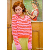redheaded woman wearing a long sleeved stripy sweater with v-lace pattern detail. it's stripes in colors of pink and red witht eh lower hem red and cuffs pink, this is another version of 'Mandolin'  from the Louisa Harding Winter's Muse Portraits Pattern Book
