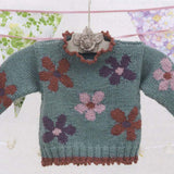 close up image of psoy sweater knitting pattern from louisa hardings enchanted garden book. a little girls sweater hangs on a beautiful hanger the main color is a soft sage green with intarsia flowers in purple pink and red