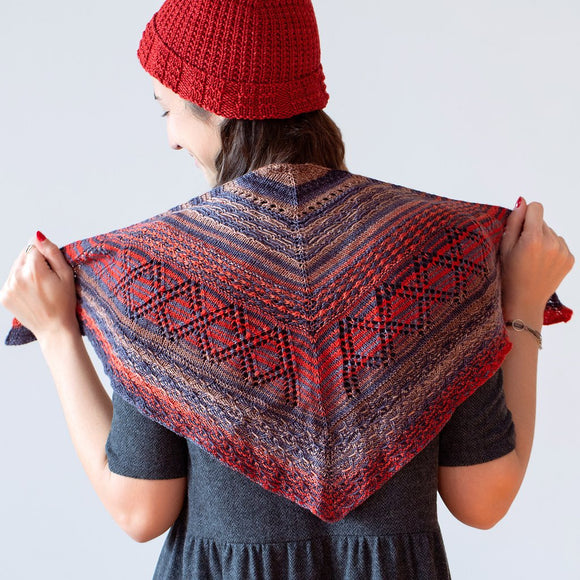 woman wearing a knitted mini shawl in stripes of red, grey and tan with lace detail, the stitch play shawl designed by marin melchior marinja knits