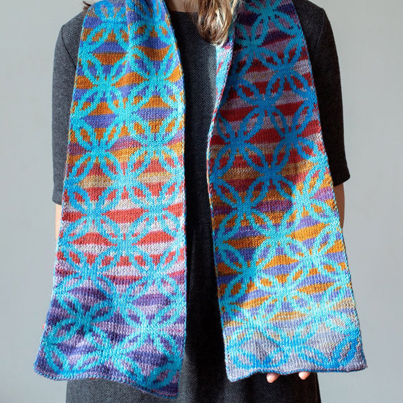 woman wearing marin melchoirs coffee circle double knit scarf in urth yarns uneek and monokrom fingering colors of blue and rainbow she's holding it out flat to show the circular design