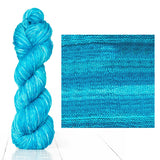Urth Yarns composite image knitted swatch and twisted hank in colors of aqua blue 3057