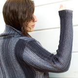 Close up of the monokrom cardigan showing a detail of how the stitching on the arms and body connect, and creat elongated stripes that run along the length of the arm with a garter stitch cuff