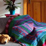 remy's wrap as a throw blanket in ridch colrs of forest green, red, purple and magenta draped over a couch