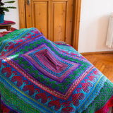 remy's wrap as a throw blanket in ridch colrs of forest green, red, purple and magenta draped over a counch