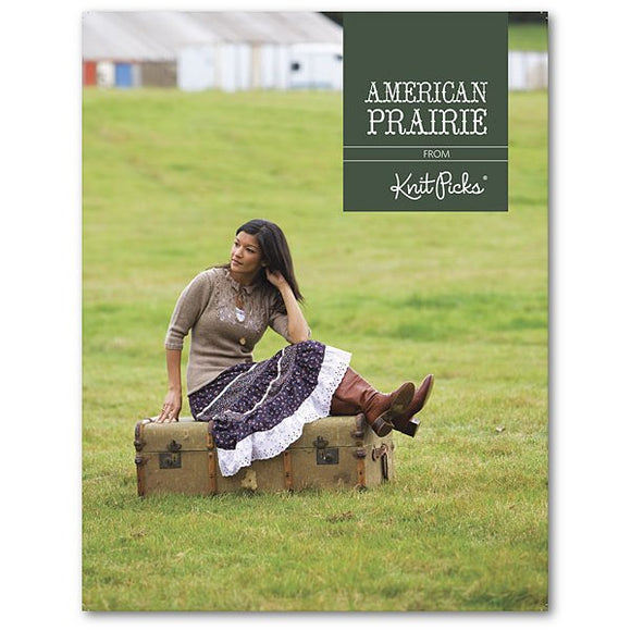 cover of knit picks american prairie knitting pattern book showing a woman sitting in a field wearing a fitted tan sweater and a patterned country skirt
