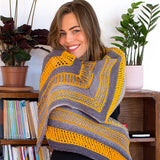 Image of maya shawl wrap knit in yellow and grey wrapped around a young lady with brioche stitches and eyelets with yarn overs