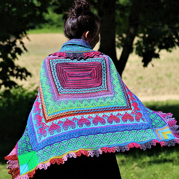 a woman wearing marin melchoirs remy's wrap in colors of lime green, magenta, and blue with stitch patterns of hearts, lace and colorwork