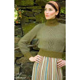 woman wearing a high waisted turtelenck knitted sweater with a angular cable pattern that runs right down the front, The neck, lower hem and cuffs feature a large ribb pattern in a moss green with the body of the sweater is in medium green