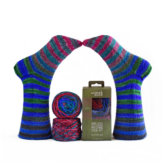 two model feet wearing blue striped socks, plus two mini balls of matching hand dyed yarn and a box of yarn showing the urht uneek sock packaging