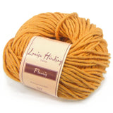 one ball of louisa hardings fleuris yarn in a golden mustard yellow color the yarn is super bulky and solid color