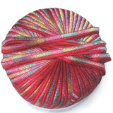 image of beach ribbon yarn by filatti FF a ribbon yarn where one havlf is solid red and the other half is a kaleidoscope of colors green pink yellow