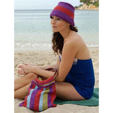 beachcomber pag and matching pearl hat Knitting pattern from louisa hardings beachcomber accessories pattern book. a woman is sitting at the beach with a brightly colored striped bag and a purple and red knitted hat