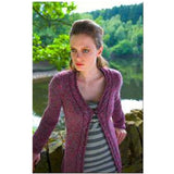 Beckmickle Long Cardigan  from Louisa Harding's Winter's Muse Landscapes Pattern Book. A Woman Stands by a river wearing a long mauve cardigan that is fastened at the chest, it features a cable pattern that runs down the sides of the neckline and front