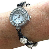 close up image of a bracelet with braided black cord  and diamond encrusted round beads. the face of the watch is set with diamonds all the way around the face with a white background and black bold numbers to easily read the time