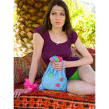 Blossomcrown Knit purse beach bag knitting pattern from Louisa Hardings Hummingbirds Pattern book. a Woman is sitting in a cabana holding a drawstring purse knitted in light sky blue, it's embelished around the opening and on the surface of the bag with little crocheted colorful flowers