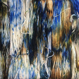 close up image of unwound yarn hanks detailing the way thei colors appear on the yarn strand. the base yarn is white which shows through a bit with speckles of sapphire blue, dark brown, light brown and golden ochre
