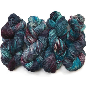 four hanks of hand dyed yarn in rich deep blues and burgundy are lined up next to eachother. The blues are rich and deep, reminiscent of a  storm brewing over teh ocean at dusk. and the purples also are very dark in some places its more mulberry, in others it puddles into a deep wine. There are still places where the undyed white strand is poking through like bit os silver cloud making it way through the landscape