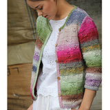 Woman standing wearing a white top and a knitted cardigan with a basketweave pattern where the stockinet squares feature a little flower-esque lace pattern. The cardigan is very bright and colorful with lots of floral reference like pinks, greens, & purples. The Cardigan has a thin sliver of rib stitch running around all the edges. There are also brown wooden buttons sewn onto the cardi.