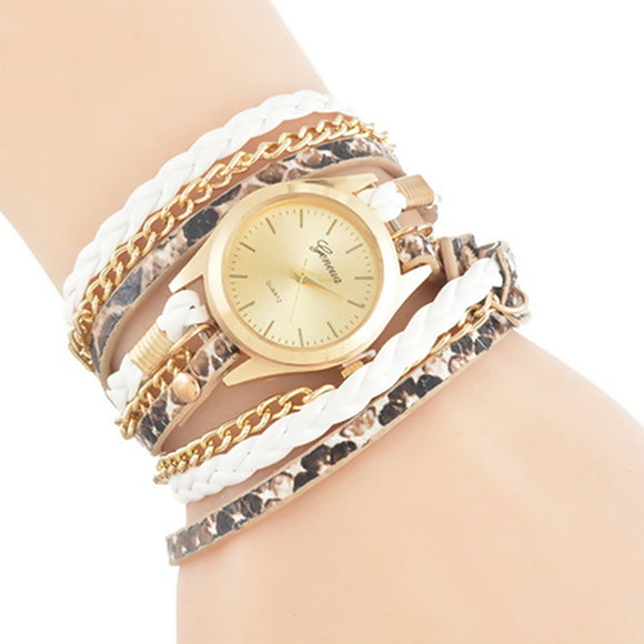 close up image of a fashion bracelet watch on woman's wrist the watch face is gold with three strands with gold chain, faux snake skin, and white faux leather braid. the three strands are wrapped around the wrist three times.