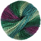 maypole yarn bulky boucle ball seen from top down. Colors shown are hunter green soft mint green, deep blue green, and purple