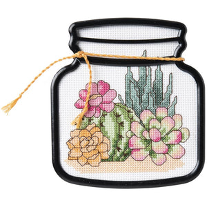 image of an adorable cross stitch of cactuses in a black plastic frame shaped like a terrarium jar. simplle little cross stitch for beginners
