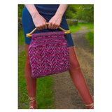 Cragwood Purse  from Louisa Harding's Winter's Muse Landscapes Pattern Book. A Close up Shot of a knitted purse with lots of textural stitch work, knit in shades of fuchsia, and mauve, with hints of glitter