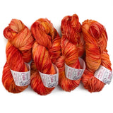 four hanks of yarn twisted up and layed next to eachother in a row. The color of the yarns is speckled with reds, oranges and peachy creams, the hanks feature yanr labels showing the branding 'about the color'