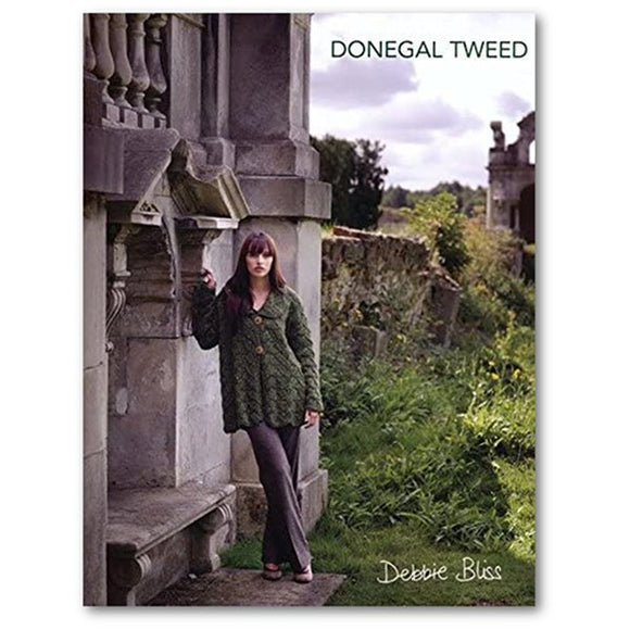 front cover of debbie bliss donegal tweed pattern book  with woman standing at churhc ruins wearing a leaf patterned knit sweater