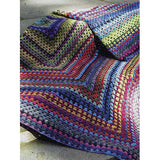 image of crocheted blanket or throw made up of one giant granny square in bright rainbow colors of blue green and fuschia
