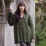 woman leaning against a church wearing a cozy cardigan in forest green with two buttons along the chest. the knit stitches a a lacy pattern that looks like layers fo leaves