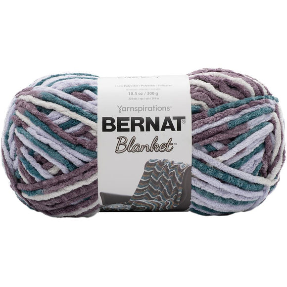 bernat blanket yarn in elderberry color a skein of yarn with variegated shades of light grey teal and soft plum purple with a chenille textured strand