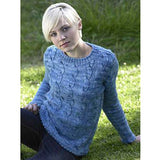 woman seated on the grass wearing a long sleeved medium blue vertically cabled pullover. emma sweater from jenny watson