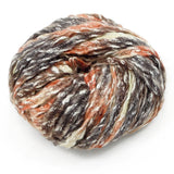 image of feza's peria sevia yarn, this ball of yarn looks like a flat felted ribbon with selvadge sewing down the center of the ribbon there are lots of colors in this strand, white is flecked throughout the whole strand and then it varies from a peachy pink to grey and medium brown