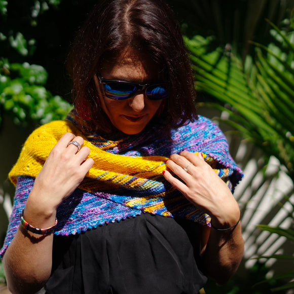 woman wearing free your fade shawl by andrea mowry knit in colors of bright yellow, magenta purple and blue standing in front of a tropical leafy background