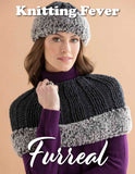 woman standing with arms crossed wearing a knitted black tight capelet with a large ribbed stitching pattern and a black mathing hat. Both the hat and capelet are trimmed in 2 tone furreal faux fur in dark and light grey