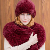 blond woman wrapped in a bright burgundy stole around her shoulders withe a matching furry hat reminiscent of russian fashion