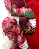 two hanks of christmas sock yarn sitting on a background of red an white faux fur. the hanks are dyed in light and dark shades of red with speckles and pops of green. it is evident in the darker parts of the yarn that there is some silver sparkle spun into the fiber