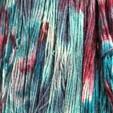 a close up of our hand dyed dk yarn with shades of light an dark blue and stains of mulberry wine
