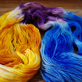 looking sidelong at caribbean party yarn it has been unfurled so we can better see the color pattern, 2/5 cobalt blue, 2/5 sunshine yellow, and 1/5 purple between the blue and yellow sections